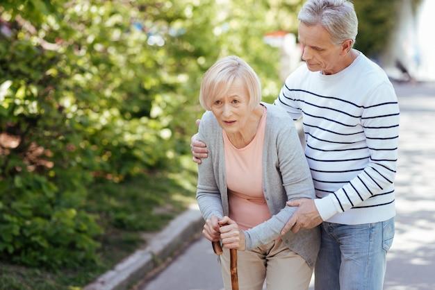 Aufmerksamer, liebevoller, alternder mann, der sich um seine alte frau kümmert und ihr hilft, schritte zu machen, während er die frau umarmt und im park spazieren geht