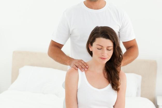 Aufmerksamer mann, der seiner schönen frau eine rückenmassage tut