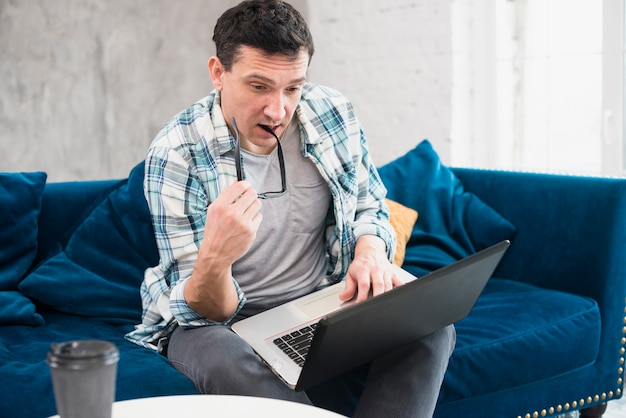 Aufmerksamer mann, der zu hause laptop betrachtet