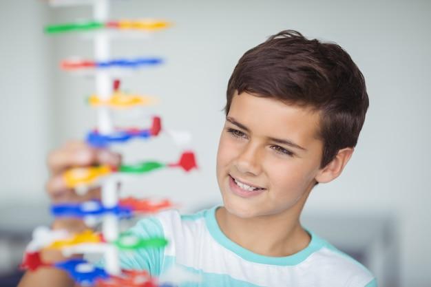 Aufmerksamer schüler experimentiert molekülmodell im labor