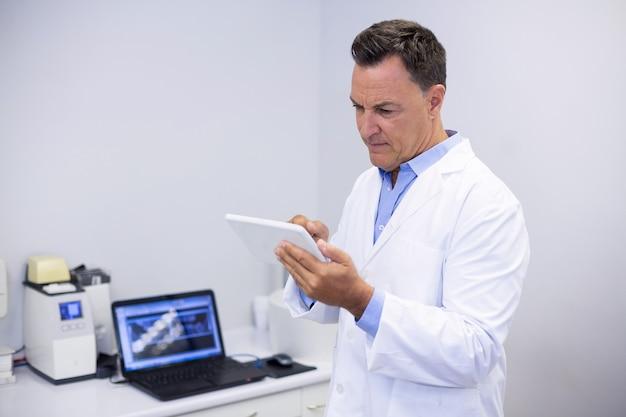 Aufmerksamer zahnarzt mit digitalem tablet
