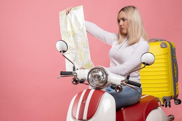 Aufmerksames blondes mädchen der vorderansicht auf moped, das karte betrachtet