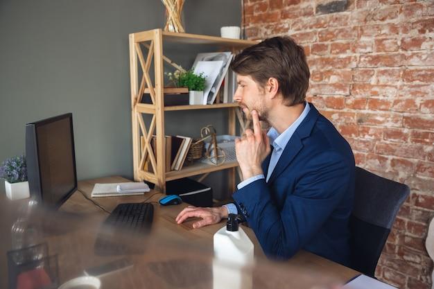 Aufmerksames lesen, analysieren von informationen. junger mann, manager, der nach der quarantäne in sein büro zurückkehrt, fühlt sich glücklich und inspiriert. rückkehr ins normale leben. business, finanzen, emotionen konzept.