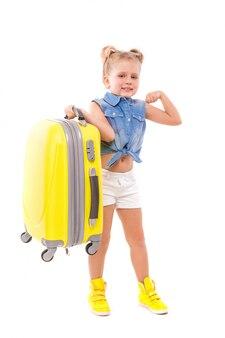 Aufmerksames nettes kleines mädchen im blauen hemd, in den weißen kurzen hosen und in der sonnenbrille halten gelben koffer