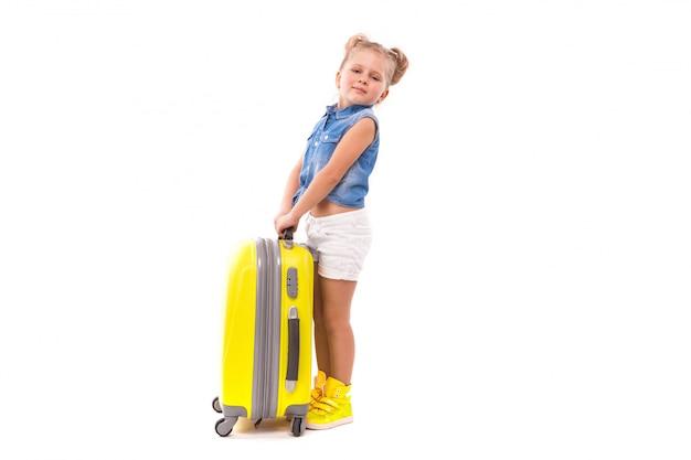 Aufmerksames nettes kleines mädchen im blauen hemd, in den weißen kurzen hosen und in der sonnenbrille stehen nahe gelbem koffer