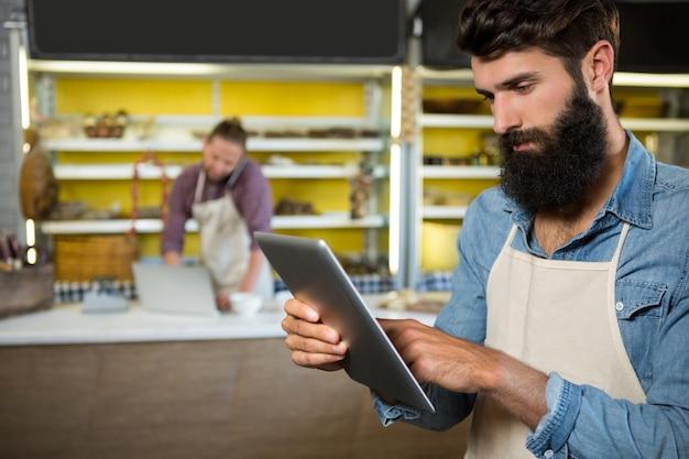 Aufmerksames personal mit digitalem tablet am bäckertisch