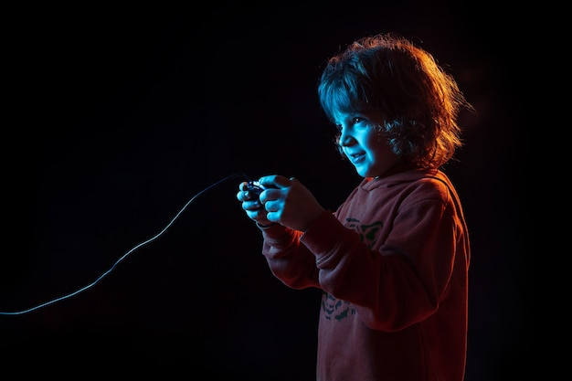 Aufmerksamkeit beim spielen von videospielen. porträt des kaukasischen jungen auf dunklem studiohintergrund im neonlicht. schönes lockiges modell. konzept der menschlichen emotionen, gesichtsausdruck, verkauf, werbung, moderne technologie, gadgets.