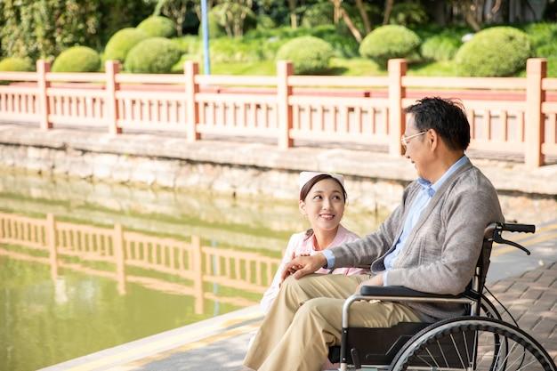 Aufmerksamkeit einer krankenschwester mit einem alten mann im rollstuhl