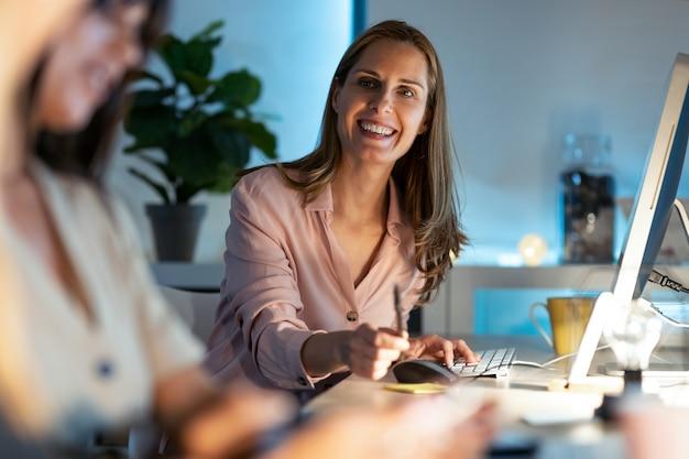 Aufnahme der lächelnden schönen reifen geschäftsfrau, die mit ihren kollegen spricht, während sie mit dem computer im büro arbeitet.