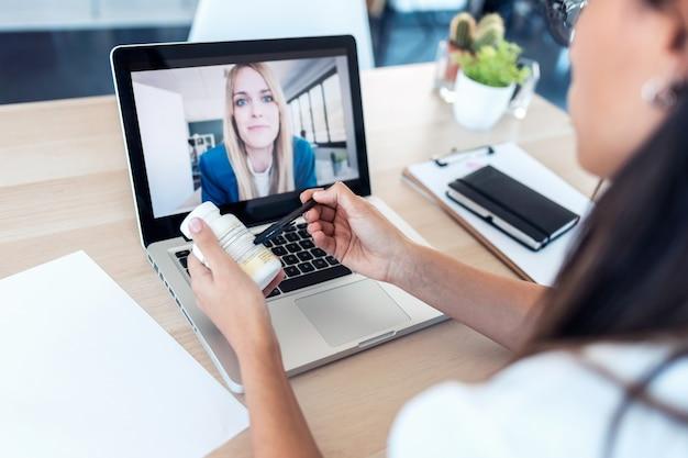 Aufnahme der rückansicht eines arztes, der eine patientin behandelt und medikamente über einen videoanruf mit dem laptop zu hause verschreibt.