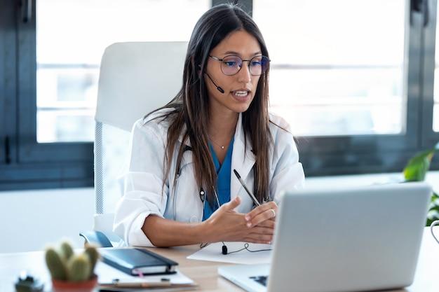 Aufnahme einer ärztin, die mit kollegen über einen videoanruf mit einem laptop in der konsultation spricht.