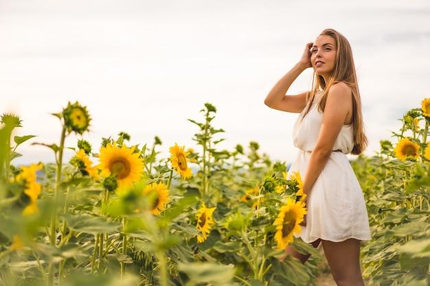 Aufnahme einer attraktiven blonden frau in einem weißen kleid, die in einem sonnenblumenfeld posiert