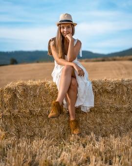 Aufnahme einer attraktiven frau in einem weißen kleid, die auf einem heuhaufen sitzt und in die kamera schaut