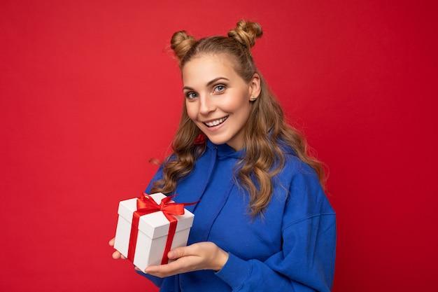 Aufnahme einer attraktiven, glücklich lächelnden jungen blonden frau, die über einer roten hintergrundwand isoliert ist und einen blauen, trendigen hoodie trägt, der eine geschenkbox hält und in die kamera schaut