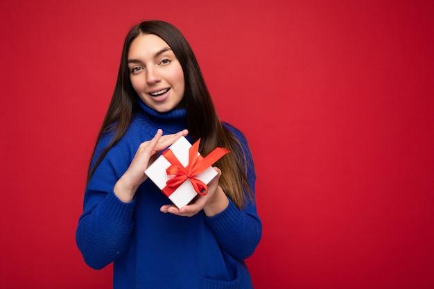 Aufnahme einer attraktiven, glücklich lächelnden jungen brünetten frau, die über einer roten hintergrundwand isoliert ist und einen blauen lässigen pullover trägt, der eine weiße geschenkbox hält und in die kamera schaut. freiraum