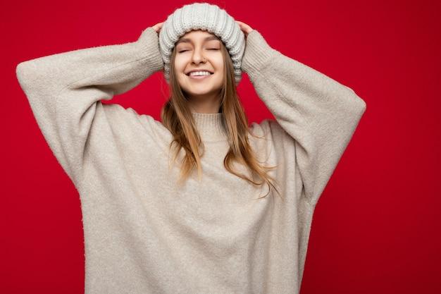 Aufnahme einer attraktiven, glücklich lächelnden jungen dunkelblonden frau, die isoliert über einer roten hintergrundwand steht und beige warmen pullover und beige wintermütze trägt und mit geschlossenen augen genießt.