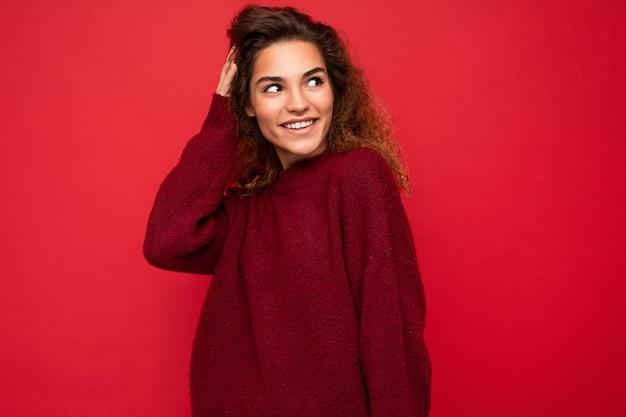 Aufnahme einer attraktiven, glücklich lächelnden jungen frau, die ein lässiges outfit trägt, das isoliert über bunt steht