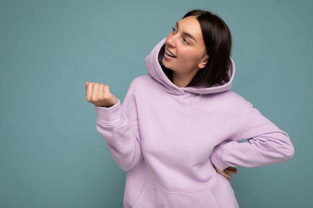 Aufnahme einer attraktiven, glücklich lächelnden jungen frau, die ein lässiges outfit trägt, das isoliert über buntem hintergrund steht, mit leerem raum, der zur seite schaut.