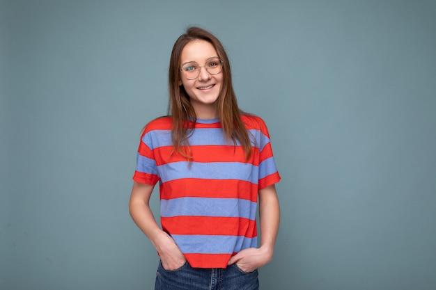 Aufnahme einer attraktiven, positiv glücklich lächelnden jungen brunet-frau, die eine stilvolle optische brille trägt, lässig gestreiftes t-shirt, das isoliert über blauer hintergrundwand steht und in die kamera schaut. freiraum