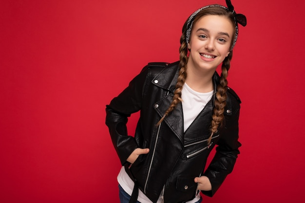 Aufnahme einer attraktiven, positiv lächelnden, brünetten kleinen weiblichen teenagerin mit zöpfen, die stylisch trägt