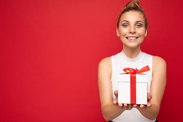 Aufnahme einer attraktiven, positiv lächelnden jungen blonden frau, die über einer bunten hintergrundwand isoliert ist und das alltägliche trendige outfit trägt, die geschenkbox hält und in die kamera schaut. platz kopieren