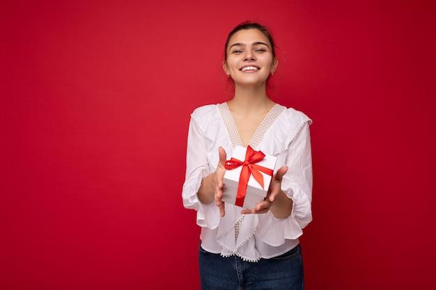 Aufnahme einer attraktiven, positiv lächelnden jungen brünetten frau, die über einer bunten hintergrundwand isoliert ist und ein alltägliches trendiges outfit trägt, das eine geschenkbox hält und in die kamera schaut
