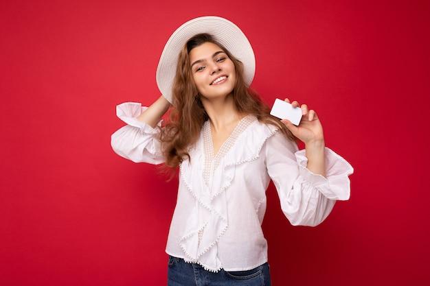 Aufnahme einer attraktiven, positiv lächelnden jungen dunkelblonden frau mit weißer bluse und weißem hut, die auf rotem hintergrund isoliert ist und kreditkarte in die kamera schaut.
