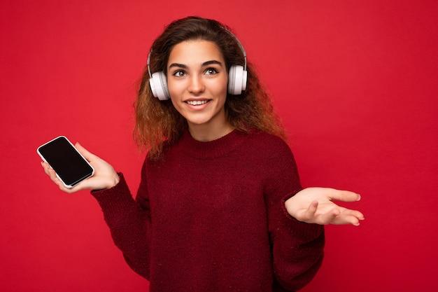 Aufnahme einer attraktiven, positiven jungen, lockigen frau, die einen dunkelroten pullover trägt, isoliert auf rot