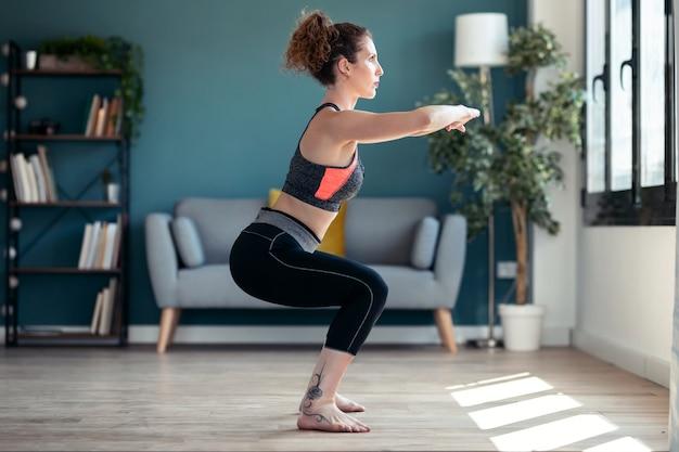Aufnahme einer attraktiven sportlichen jungen frau, die zu hause hypopressive übungen im wohnzimmer macht.