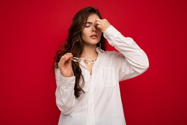 Aufnahme einer attraktiven traurigen traurigen verärgerten jungen lockigen brünetten frau, die weißes hemd und optisches trägt