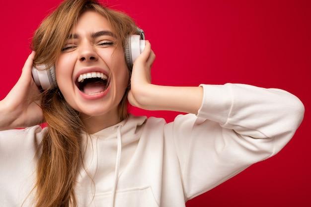 Aufnahme einer attraktiven, verrückten, positiven jungen blonden frau, die einen weißen hoodie trägt, isoliert über bunt