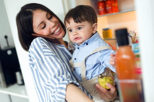 Aufnahme einer beschäftigten jungen mutter mit ihrem baby, die am telefon spricht, während sie die kühlschranktür in der küche zu hause öffnet.