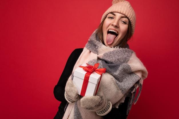 Aufnahme einer charmanten, glücklich lächelnden jungen brünetten frau, die über einer roten hintergrundwand isoliert ist und winter trägt?