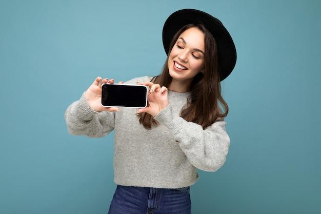 Aufnahme einer charmanten jungen glücklichen frau mit schwarzem hut und grauem pullover, die das telefon mit blick auf die hält