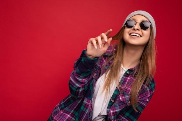 Aufnahme einer charmanten lächelnden erwachsenen blonden frau, die auf rotem hintergrund isoliert ist und ein lila freizeithemd und eine stilvolle sonnenbrille trägt, die in die kamera schaut und spaß hat