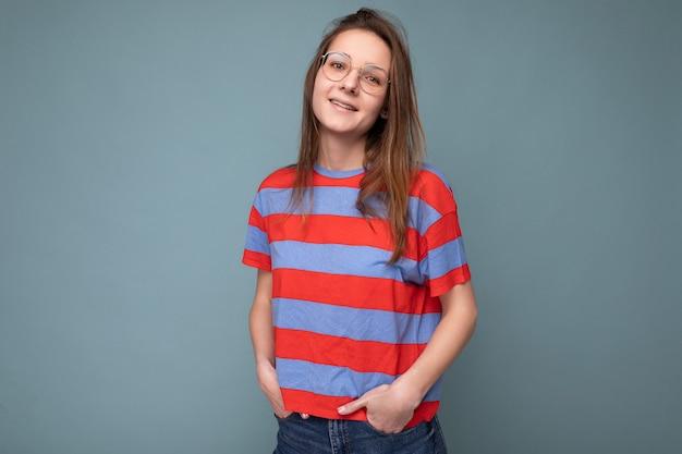 Aufnahme einer charmanten lächelnden, süßen jungen brunet-frau, die eine optische brille trägt, lässig gestreiftes t-shirt