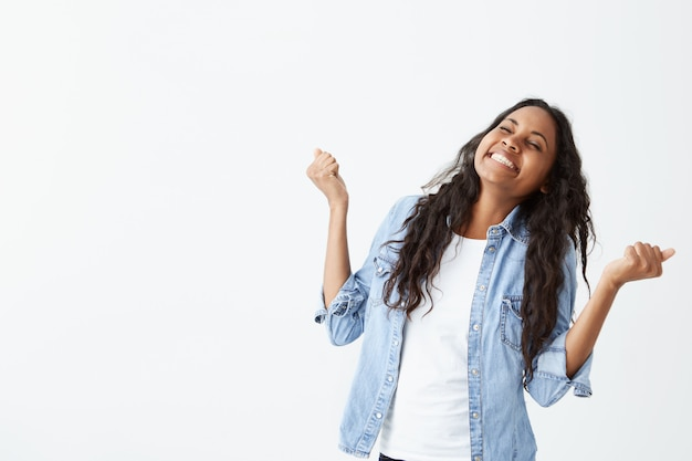 Aufnahme einer dunkelhäutigen erfolgreichen frau mit langen, welligen haaren, die ein jeanshemd trägt und vor aufregung die fäuste ballt, um ihre leistung und ihren erfolg zu feiern.