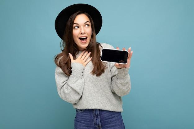 Aufnahme einer erstaunten, charmanten jungen, glücklichen frau mit schwarzem hut und grauem pullover, die das telefon mit blick auf die seite isoliert im hintergrund hält. mock-up, ausschnitt, kopienraum