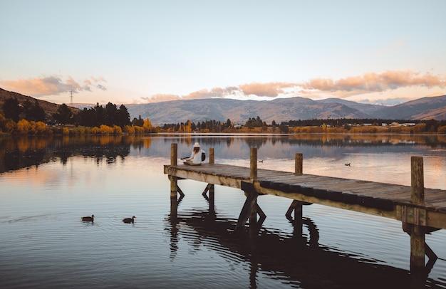 Aufnahme einer frau, die auf dem pier sitzt und gitarre in cromwell, neuseeland spielt?