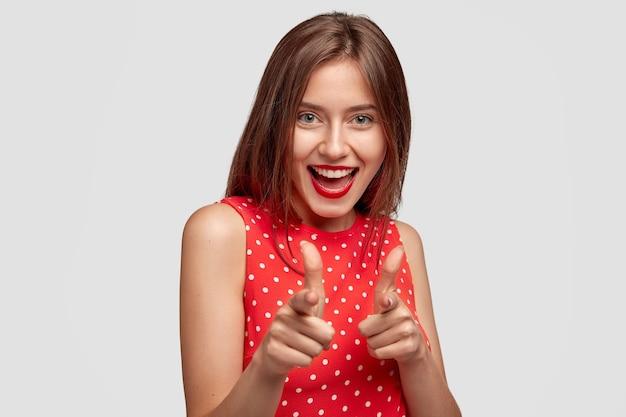 Aufnahme einer fröhlichen jungen frau mit positiven ausdruckspunkten mit beiden zeigefingern, isoliert über weißer wand. fröhliche frau zeigt waffengeste, grüßt freund, billigt idee