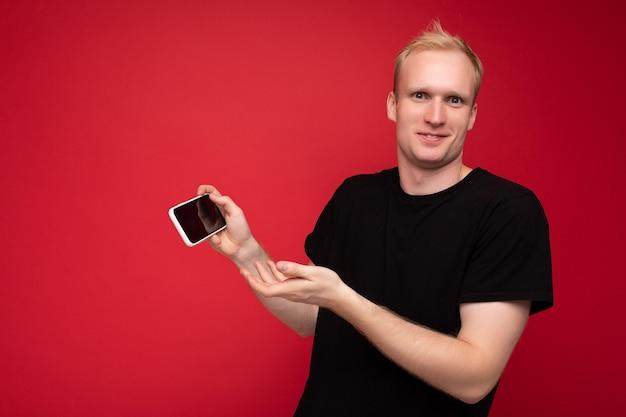 Aufnahme einer gutaussehenden lächelnden blonden jungen männlichen person, die ein schwarzes t-shirt trägt, das isoliert auf rotem hintergrund steht, mit kopienraum, der smartphone hält, das telefon in der hand mit leerem display für mockup-punkt zeigt