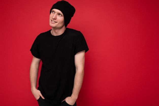 Aufnahme einer gutaussehenden positiven jungen männlichen person, die isoliert über einer roten hintergrundwand steht und ein schwarzes t-shirt für mockup und schwarzen hut trägt und zur seite schaut und träumt. freiraum
