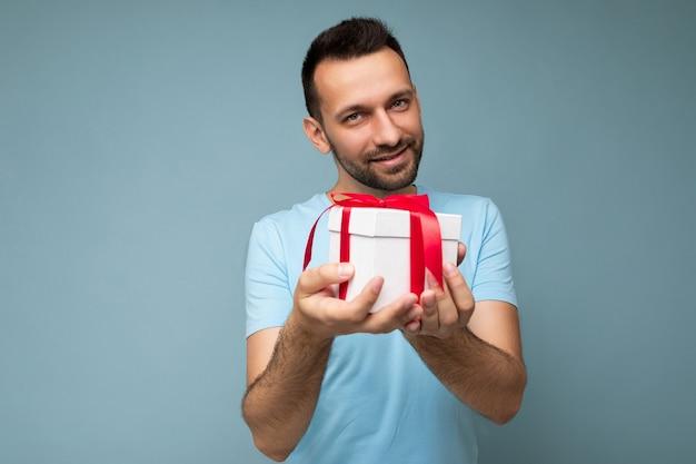 Aufnahme einer hübschen, glücklichen, brünetten, bärtigen jungen männlichen person, die über einer blauen hintergrundwand isoliert ist