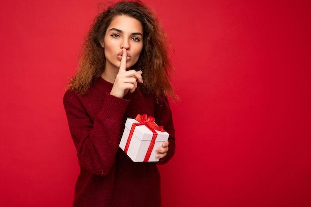 Aufnahme einer hübschen jungen, brünetten, lockigen frau, die über einer roten hintergrundwand isoliert ist und einen roten pullover trägt?