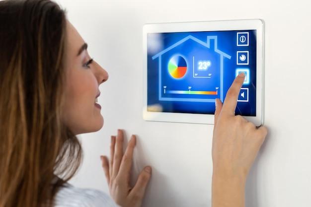 Aufnahme einer hübschen jungen frau, die das hausautomationssystem auf einem digitalen tablet verwendet, um die temperatur zu regulieren.