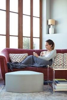 Aufnahme einer hübschen jungen frau, die ihr handy benutzt, während sie zu hause kaffee auf dem sofa trinkt.
