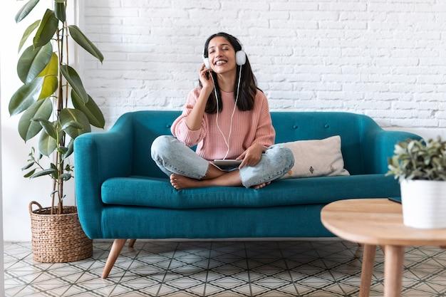 Aufnahme einer hübschen jungen frau, die mit digitalem tablet musik hört und sich entspannt, während sie zu hause auf dem sofa sitzt.