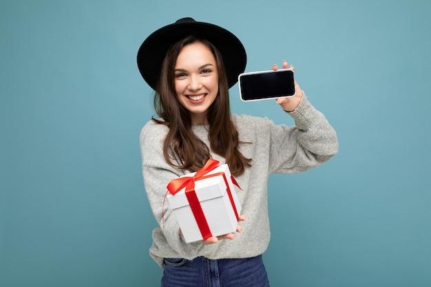 Aufnahme einer hübschen lächelnden positiven jungen brünetten frau, die über blauer hintergrundwand isoliert ist