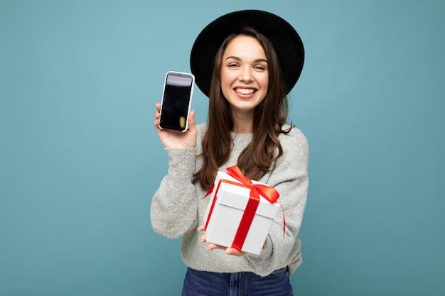 Aufnahme einer hübschen lächelnden positiven jungen brunet-frau, die auf blauer hintergrundwand isoliert ist und schwarz trägt?