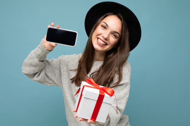 Aufnahme einer hübschen lächelnden positiven jungen brunet-frau, die über blauer hintergrundwand isoliert ist?